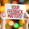 hands holding sign that says your feedback matters