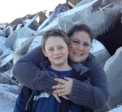 Photo of mom and son smiling in front of rocks at beach