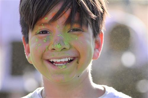 Student smiling with green paint on his face