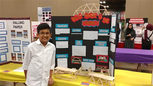 student standing in front of science fair display