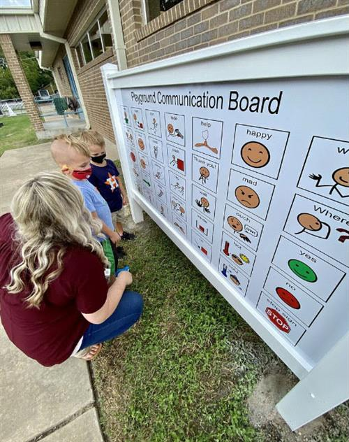 teacher and students looking at communication board